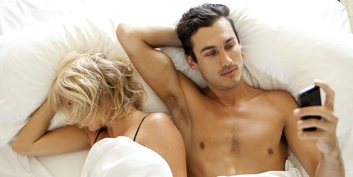 couple in bed man looking at phone shirtless